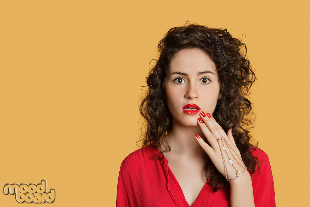 Portrait of a shocked woman over colored background