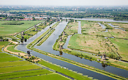 Nederland, Zuid-Holland, Kinderdijk, 04-07-2006; boezems van de polder Nieuw-Lekkerland, onderdeevan de Alblasserwaard; windmolens gebruikt voor het droogmalen van de polder en voor de waterhuishouding (het bemalen); de molens behoren bij het wereld cultureeerfgoed (Unesco); links van de boezem het dorpje Kinderdijk, aan de andere kant van de rivier de Lek , aan de horizon Krimpen aan de IJsse(met hoogbouw); Windmills for pumping the water out of the polder (the drainage). The Mill Network at Kinderdijk-Elshout is part of the  World Heritage of Unesco. More pics available of this location..luchtfoto (toeslag); aerial photo (additional fee required); .foto Siebe Swart / photo Siebe Swart