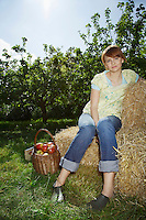 Woman sitting on hay bales near orchard portrait