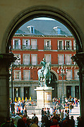SPAIN, MADRID, MONUMENTS Plaza Mayor; the heart of the old city, begun in 1617; with a statue of Felipe III seen through arch