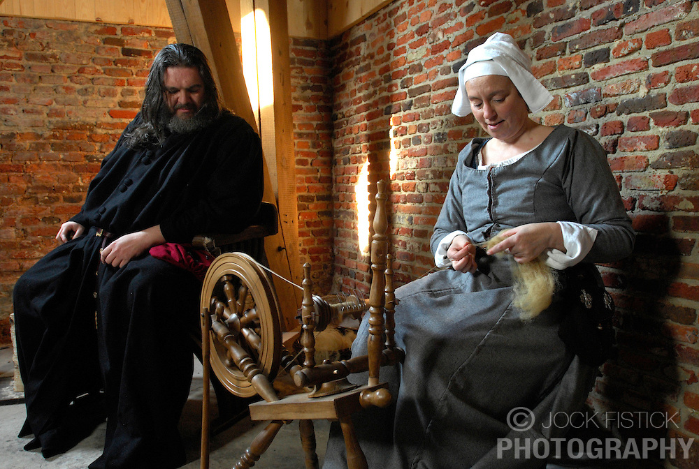 AARSCHOT, BELGIUM - MARCH-14-2007 -  Daniel Grand Jean Watches as Maris Lowers works at a spinning wheel in the Sint-Rochustoren Tower, a medieval tower that was closed to the public for 600 years. Jean and Lowers are members of the Orde Van De Hagelanders, a group who recreates medieval life and convinced the city of Aarschot to allow them to restore the tower to its medieval glory. (Photo © Jock Fistick)
