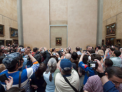 Huge crowds of tourists trying to see Mona Lisa painting by Leonardo da Vinci at The Louvre museum in Paris France