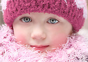 A portrait of a young Czech girl bundled up for cold winter weather. Her pink outfit compliments her beautiful big blue eyes.