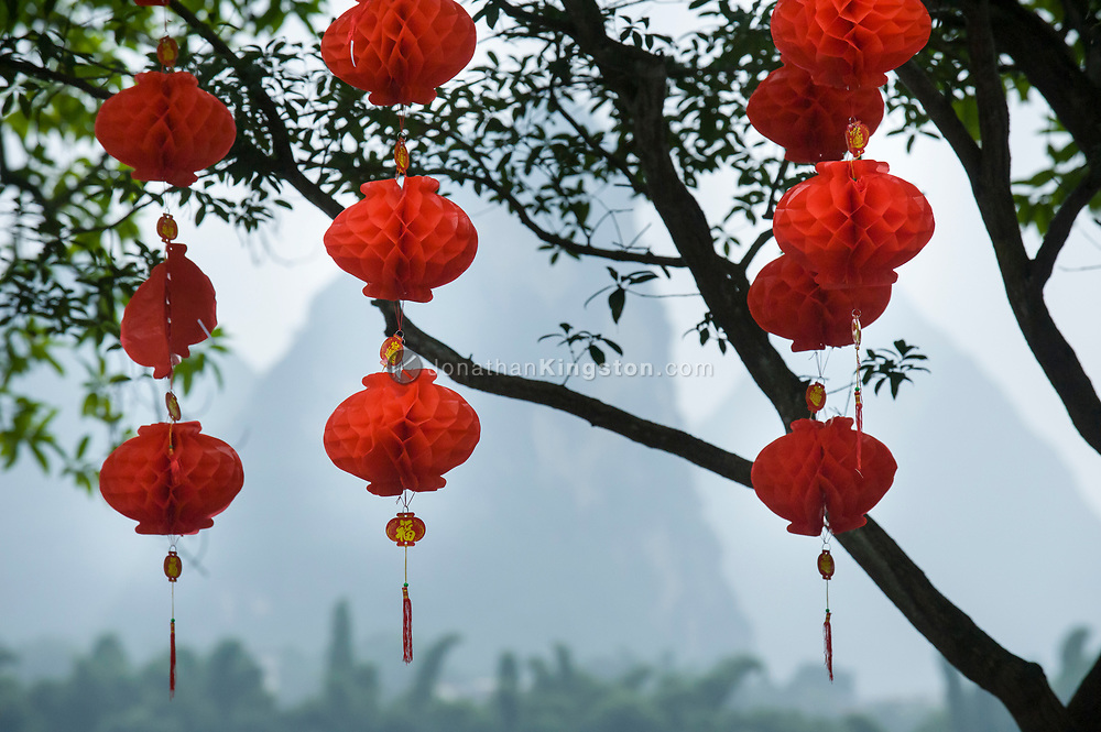 Red decorative paper globes hang from tree branches in celebration of Chinese National Day in Yangshuo, China.