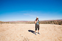 A woman stands on a sandstone slad drinking from her hydration pack at midday in Arches National Park, Utah, USA.