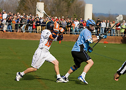 Virginia attackman Garrett Billings (19) tries to knock the ball from Johns Hopkins defenseman Eric Zerrlaut (16).  The #2 ranked Virginia Cavaliers defeated the #6 ranked Johns Hopkins Blue Jays 13-12 in overtime at the University of Virginia's Klockner Stadium in Charlottesville, VA on March 22, 2008.  The loss, in front of a record UVA crowd of 7,500, was the third consecutive overtime defeat for Hopkins, the defending national champions.