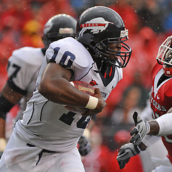 Sep 12, 2009; Piscataway, NJ, USA; Howard quarterback Floyd Haigler (10) runs around the reach of Rutgers defensive end George Johnson (31) during the first half of Rutgers' 45-7 victory over Howard in NCAA College Football at Rutgers Stadium.
