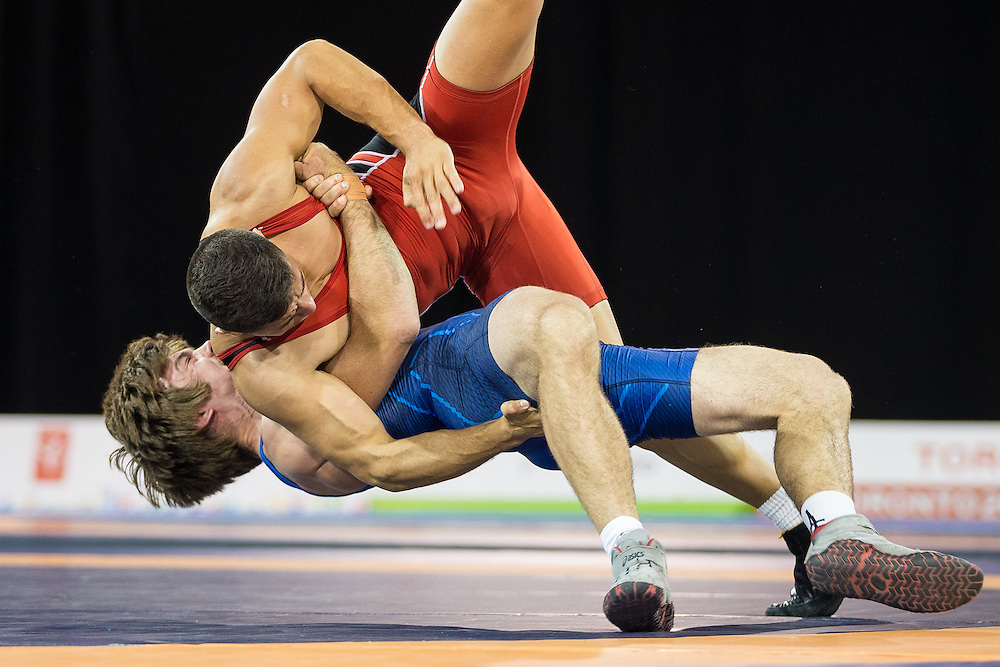 Andrew Bisek (bottom) of the United States throws Alvis Almendra of Panama during the gold medal bout in the 75kg class of the men's greco-roman wrestling at the 2015 Pan American Games in Toronto, Canada, July 15,  2015.  AFP PHOTO/GEOFF ROBINS