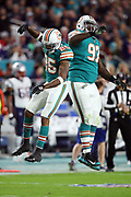 Miami Dolphins cornerback Xavien Howard (25) and Miami Dolphins defensive tackle Jordan Phillips (97) leap and celebrate after a third quarter defensive stop during the 2017 NFL week 14 regular season football game against the New England Patriots, Monday, Dec. 11, 2017 in Miami Gardens, Fla. The Dolphins won the game 27-20. (©Paul Anthony Spinelli)