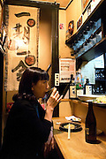 A customer enjoys a drink and some home-cooked food at Enoki, a bar-cum-eatery in Nonbeiyokjocho, or Drunkard's Alley, in trendy Shibuya district, Tokyo. Bottles of Japanese shochu bought by regular customers at Enoki are named and stored on the shelves of the tiny bar-cum-eatery in Nonbeiyokocho, or Drunkard's Alley, in Nonbeiyokocho began life immediately after World War II as group of tea houses. Though the alley is just a short walk from the central Shibuya shopping district, the rents are low due to the area being built over a river. Today 47 eateries, each with barely enough room to swing a cat, serve beer, fine wines and good, inexpensive fare.