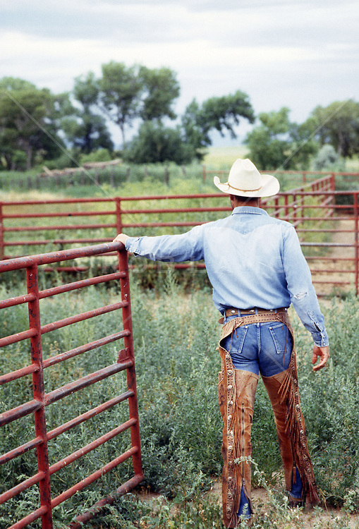 cowboy in chaps walking on a ranch