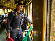 19 MARCH 2015 - AYUTTHAYA, AYUTTHAYA, THAILAND:  A conductor in the window of the Ayutthaya to Bangkok third class train. The train line from Bangkok to Ayutthaya was the first rail built in Thailand and was opened in 1892. The State Railways of Thailand (SRT), established in 1890, operates 4,043 kilometers of meter gauge track that reaches most parts of Thailand. Much of the track and many of the trains are poorly maintained and trains frequently run late. Accidents and mishaps are also commonplace. Successive governments, including the current military government, have promised to upgrade rail services. The military government has signed contracts with China to upgrade rail lines and bring high speed rail to Thailand. Japan has also expressed an interest in working on the Thai train system. Third class train travel is very inexpensive. Many lines are free for Thai citizens and even lines that aren't free are only a few Baht. Many third class tickets are under the equivalent of a dollar. Third class cars are not air-conditioned.   PHOTO BY JACK KURTZ