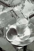 orange juice and raomance column on glass table,black and white,verticle