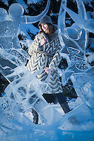 "Taylor Lee models a coat from Anchorage's ""Second Run"" with the winning entry, ""Where We Dwell"", ice sculpture by Jenny Rosenbaum and Paul Hanis during the ""Crystal Gallery of Ice"" at Town Square, Anchorage, Alaska"