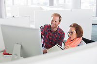 Businessman and businesswoman using computer in creative office