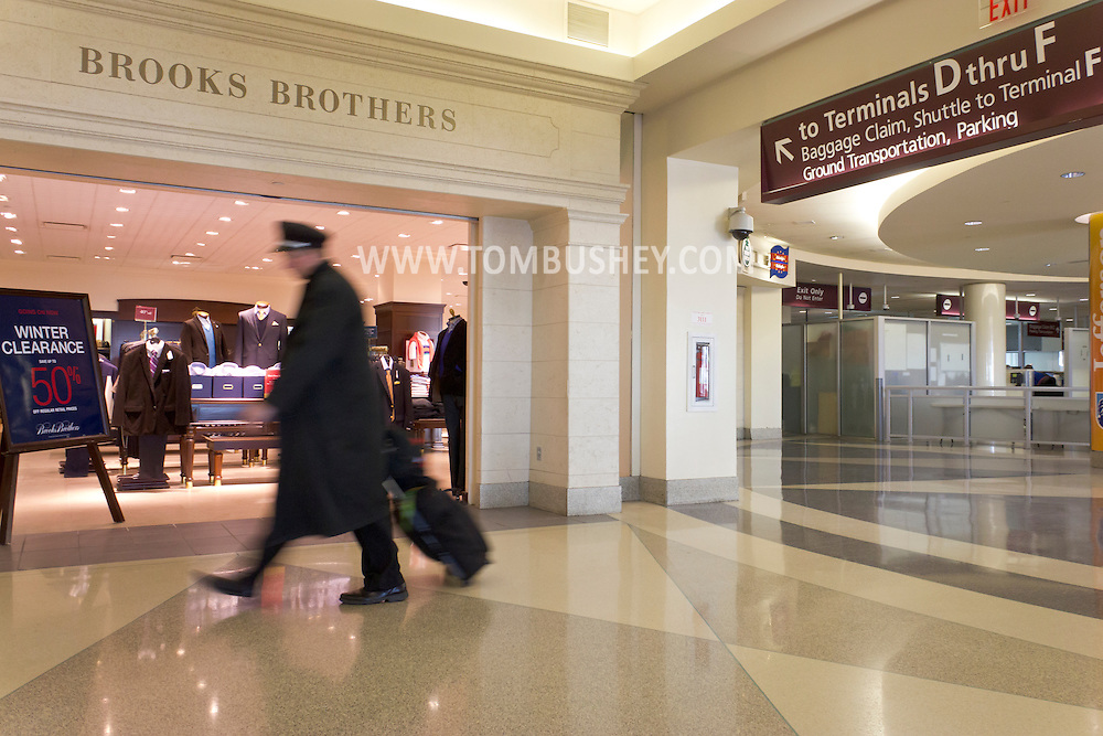 Philadelphia, Pennsylvania - A member of an airline crew walks past a Brooks Brothers store at Philadelphia International Airport on Jan. 26, 2013.
