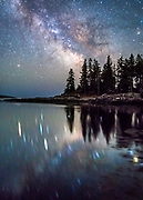 The night sky reflects in the ocean beneath a beautiful peninsula at Reid State Park in Georgetown Maine. The Milky Way can be clearly seen in the night sky.