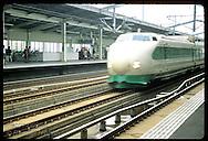 Bullet train (Shinkansen), nearing 150 mph, races thru Utsunomiya station northbound from Tokyo. Japan