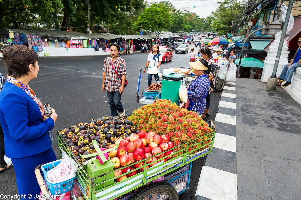 06 JUNE 2013 - BANGKOK, THAILAND:    A fruit vendor and other food vendors in front of Bobae Market on Krung Kasem Rd in Bangkok. Bobae Market is a 30 year old famous for fashion wholesale and is now very popular with exporters from around the world. Bobae Tower is next to the market and  advertises itself as having 1,300 stalls under one roof and claims to be the largest garment wholesale center in Thailand.       PHOTO BY JACK KURTZ