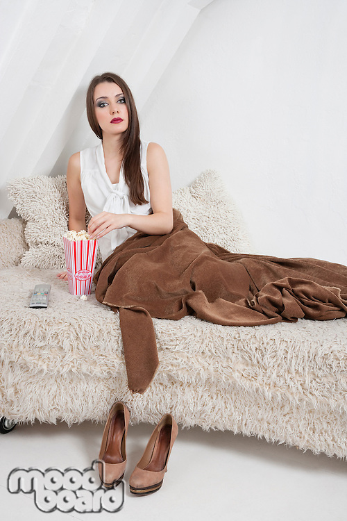 Portrait of a beautiful young woman on fur bed eating popcorn