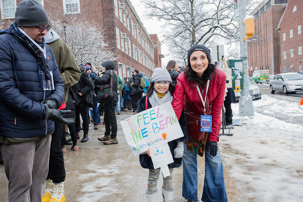 """Brooklyn, NY - 2 March 2019. A girl and her mother waint to get in to the first rally for Bernie Sanders'  2020 presidential primary at Brooklyn College. The girl carries a sign that reads """"I feel the Bern."""""""