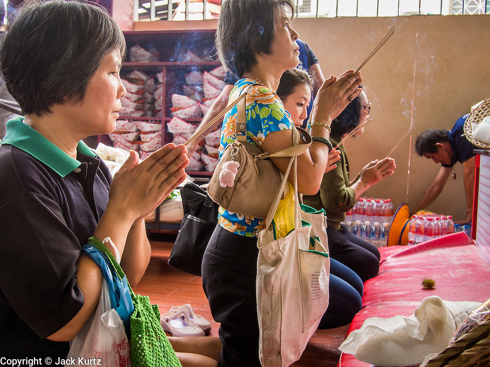 """26 AUGUST 2013 - BANGKOK, THAILAND: People pray after donating food to the Poh Teck Tung Foundation for Hungry Ghost Month in Bangkok. Poh Teck Tung operates hospitals and schools and provides assistance to the poor in Thailand. The seventh lunar month (August - September in 2013) is when the Chinese community believes that hell's gate will open to allow spirits to roam freely in the human world for a month. Many households and temples will hold prayer ceremonies throughout the month-long Hungry Ghost Festival (Phor Thor) to appease the spirits. During the festival, believers will also worship the Tai Su Yeah (King of Hades) in the form of paper effigies which will be """"sent back"""" to hell after the effigies are burnt.     PHOTO BY JACK KURTZ"""