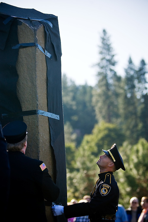 JEROME A. POLLOS/Press ..Coeur d'Alene Police officer Nick Knoll unveils a basalt column at the Fallen Heroes Plaza at Cherry Hill in Coeur d'Alene during a Sept. 11 memorial event. The column is one of two which represent the World Trade Center towers.