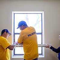 Cody Chavez, left, Jeremy Chavez and Marcie Chavez work together to mount new blinds in an apartment at Battered Families Services in Gallup Saturday.