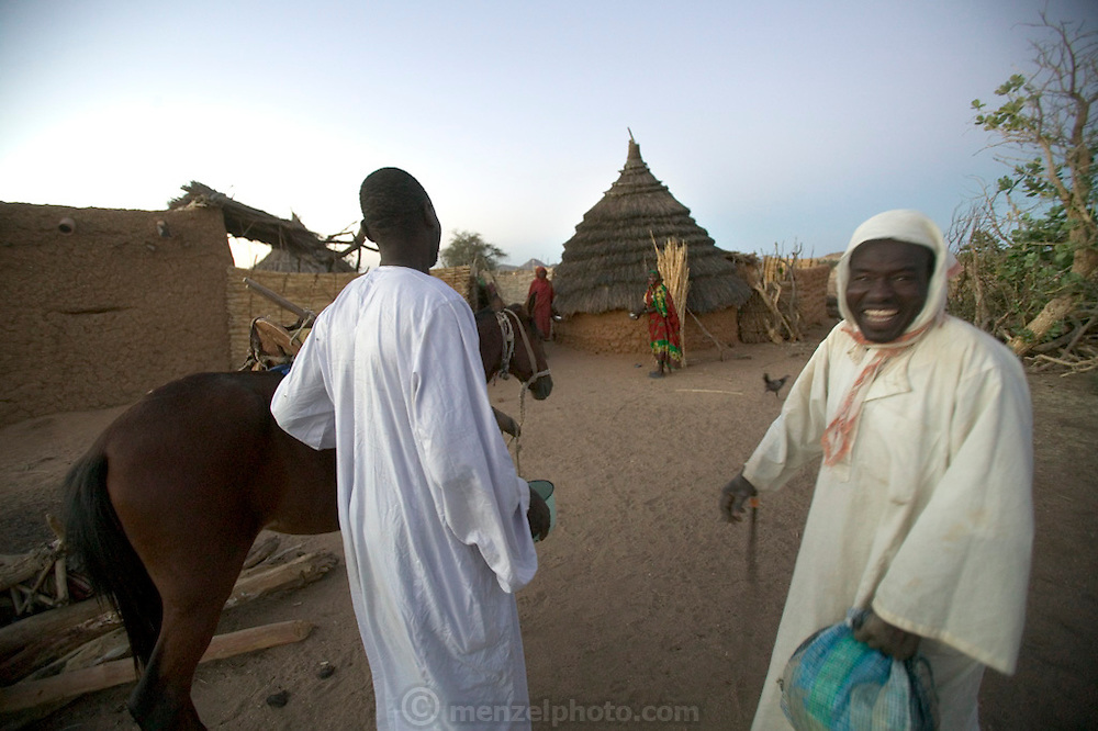 Dar es Salaam village, eastern Chad, at dawn: Mustapha Abdallah Ishakh, 46 (left) jokes with a neighbor. (Supporting image from the project Hungry Planet: What the World Eats.)