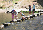 Family on stepping stones, Dovedale, Peak District national park, Derbyshire, England