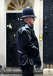 © Licensed to London News Pictures. 25/04/2012. Westminster, UK . A policeman stands on Downing Street in heavy rain in central London on April 25, 2012 Photo credit : Stephen Simpson/LNP