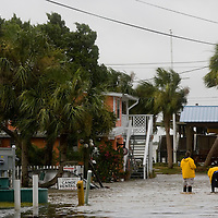 A pair of journalists stand in low lying area on Cedar Key, Florida thats was flooded from the surge associated with Tropical Storm Alberto June12, 2006. REUTERS/Scott Audette