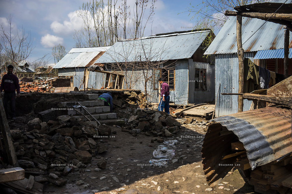 Village men rummage through the rubble of their destroyed properties in Abikarpora village on the Dal Lake, Srinagar, Jammu and Kashmir, India, on 25th March 2015. Nearly 2500 villagers including Srinagar, the capital of the state of Jammu and Kashmir, was devastated by severe floods and landslides in September 2014 the worst in 60 years, displacing millions of people, many of them children. Photo by Suzanne Lee for Save the Children