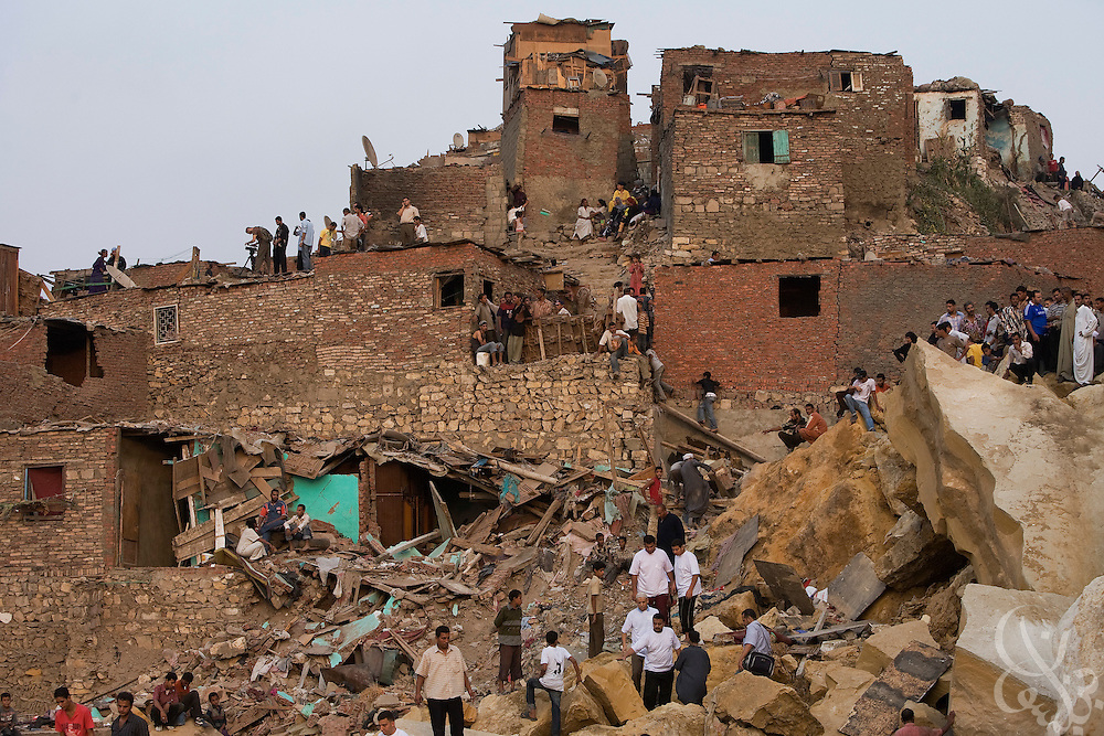 Egyptian residents of the Manshiyet Nasr shantytown search a field of giant boulders left by a rock slide that killed at least 64 and buried perhaps hundreds more Saturday September 06, 2008 on the eastern edge of Cairo, Egypt. Residents have complained that the government appears to be doing little to reach possible survivors, and have clashed with police at the site of the disaster.