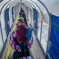 Visitors ride the covered 'magic carpet' walkway to the top of the slope to enjoy the newly-made snow during opening day at Big Bear Snowplay in Big Bear City, Sunday, Nov. 19, 2017. The local temperatures from the night time mid 20's to mid 50's in the day have made for Big Bear Snowplay to make from 6 inches to 2 1/2 foot base. Snowplay will continue to make new snow every night along with other mountain recreation areas and resorts. (Eric Reed/For The OC Register/SCNG)