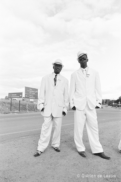 Two men traveling on foot in a rented white suit to attend a funeral, Eastern Cape province, South Africa