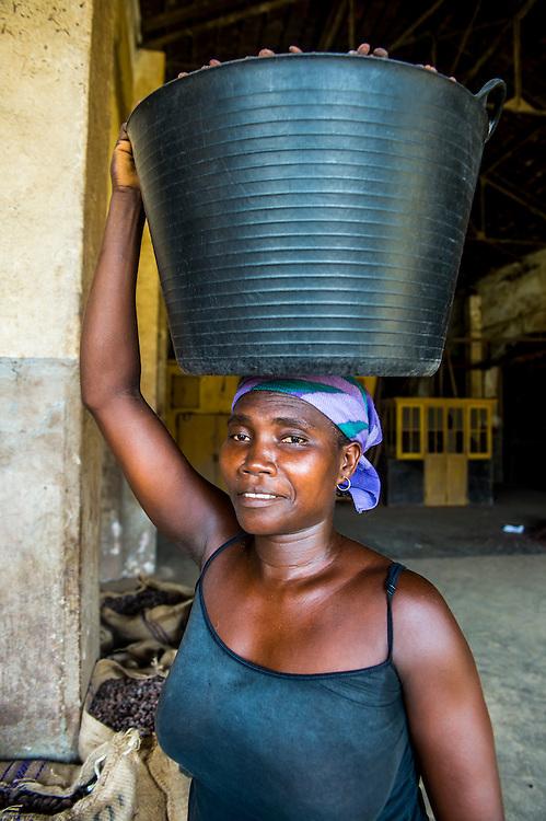 Frau mit einem Eimer voll mit Kakaobohnen auf dem Kopf