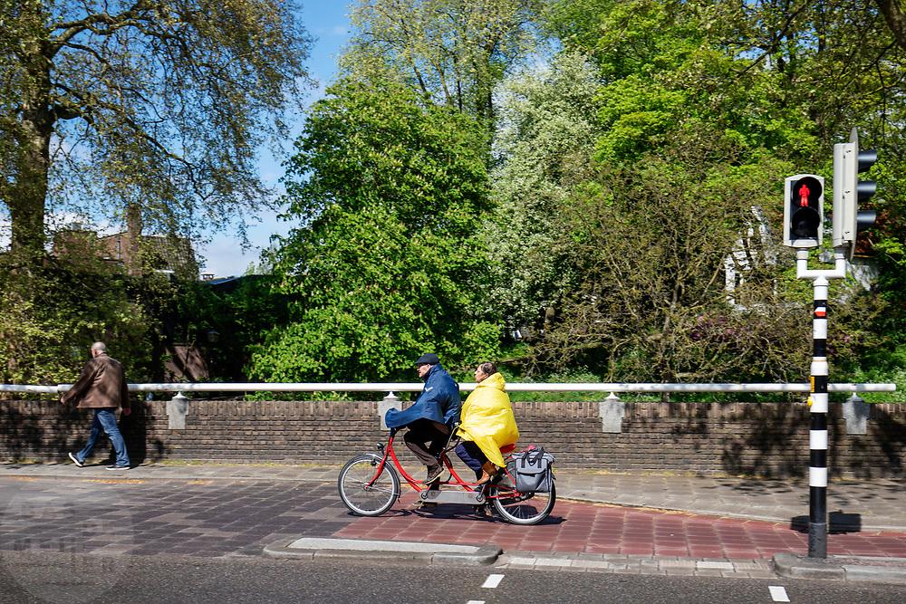 Een man en vrouw rijden op een tandem door de binnenstad van Utrecht.<br /> <br /> A man and woman ride a tandem at the city center of Utrecht.