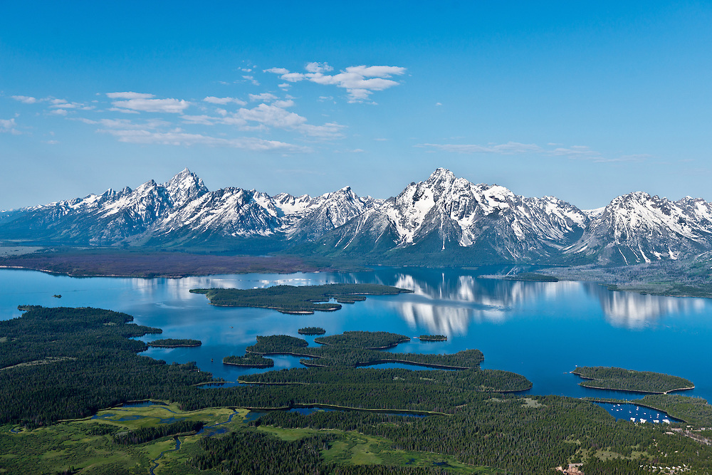Aerial view of Jackson Lake and the Teton Mountain Range in Teton National Forest on beautiful calm spring morning