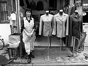 A seamstress stand next to examples of her work in a Shanghai street.