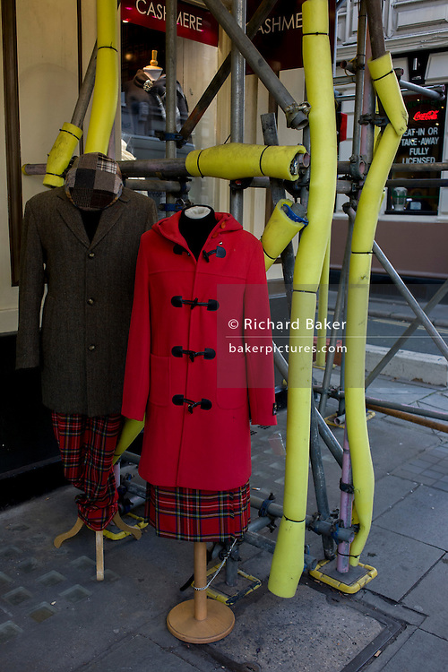 Cashmere clothing on display alongside yellow construction scaffolding sleeves in central London.