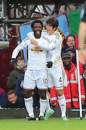 Wilfried Bony of Swansea City (left) celebrates with team mate, Ki Sung-Yueng after scoring the opening goal of the Barclays Premier League match against West Ham United at the Boleyn Ground, London<br /> Picture by Richard Calver/Focus Images Ltd +447792 981244<br /> 07/12/2014