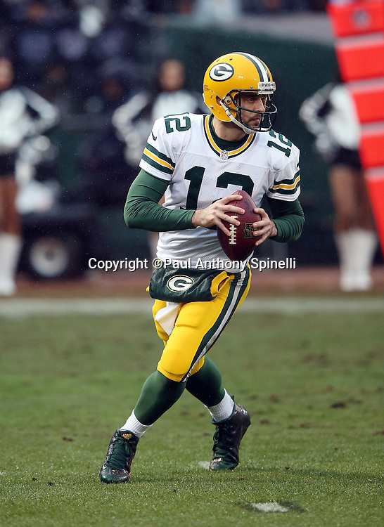 Green Bay Packers quarterback Aaron Rodgers (12) rolls out while looking to pass during the 2015 week 15 regular season NFL football game against the Oakland Raiders on Sunday, Dec. 20, 2015 in Oakland, Calif. The Packers won the game 30-20. (©Paul Anthony Spinelli)