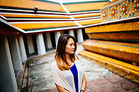 A woman walks through the Wat Pho complex in Bangkok, Thailand.