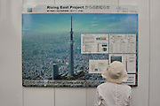 A Tourist read information about Tokyo Sky Tree under construction on a construction site wall. This new telecommunication tower will measure 634 metres when it is finished in 2011 making it the tallest structure in East Asia. Oshiage, Tokyo, Japan June 21st 2010