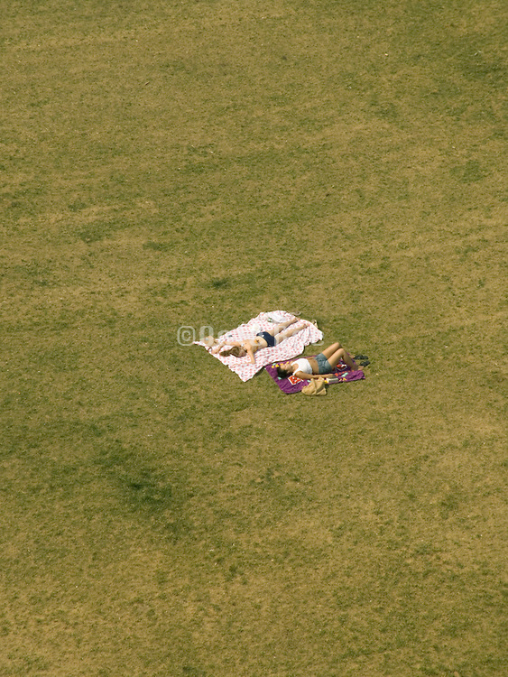 aerial view of two women laying on the grass
