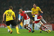 Alexis Sanchez of Arsenal battles with Lukasz Piszczek and Kevin Grobkreutz of Borussia Dortmund during the UEFA Champions League match at the Emirates Stadium, London<br /> Picture by Richard Calver/Focus Images Ltd +447792 981244<br /> 26/11/2014