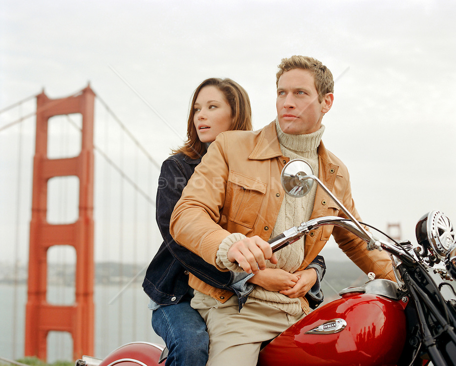 couple on a motorcycle by The Golden Gate Bridge in San Francisco, California
