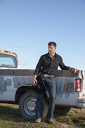 hot cowboy by an old pick up truck out in a field