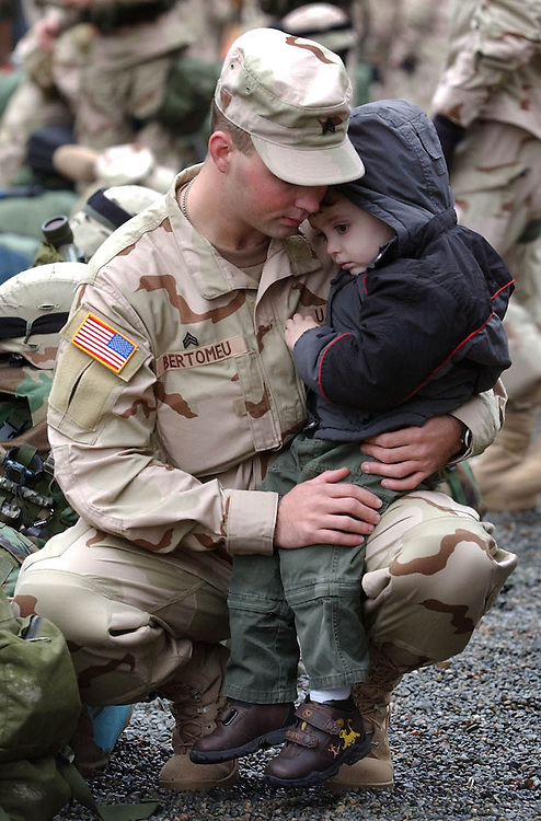 Sgt. Chris Bertomeu hugs his son Cameron, age 3, as he and members of 5th Battalion, 20th Infantry, 3rd Brigade, 2nd ID, the Army's first Stryker Brigade, prepare to depart from Ft. Lewis, Washington, on a flight to Kuwait to begin their year-long deployment in Iraq.